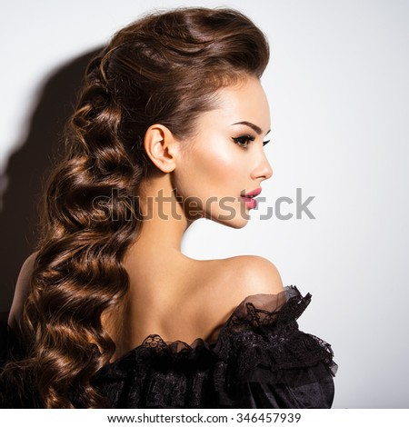 Beautiful face of an young sexy woman in black dress  posing at studio on white background - stock photo