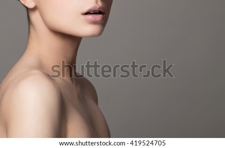 Beautiful face of young adult woman with clean fresh skin and bare shoulders. - stock photo