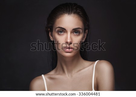 Beautiful face of young adult woman with clean fresh skin and wet hair on dark studio background - stock photo