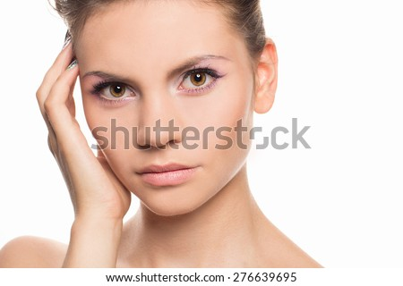 Beautiful face of young adult woman with clean fresh skin - isolated on white. Beautiful Spa Woman Touching her Face. Youth and Skin Care Concept