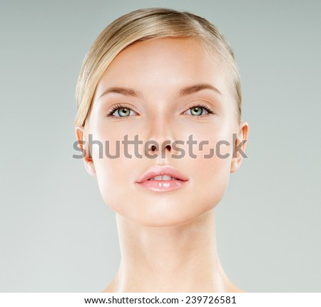 Beautiful face of young adult woman with clean fresh skin. Looking at Camera.