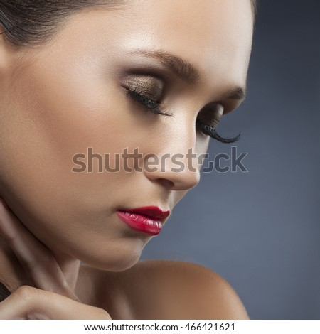 Beautiful face of young caucasian brunette woman with closed eyesand red lips, evening make-up, perfect skin. Isolated on grey background. Studio portrait.
