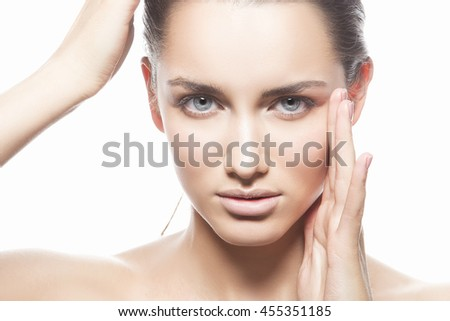 Beautiful face of young caucasian brunette woman with natural lips, make-up and blue eyes isolated on white. Touch her head. Perfect skin. Studio portrait. - stock photo