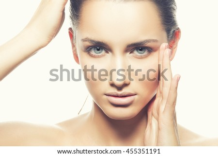 Beautiful face of young caucasian brunette woman with natural lips, make-up and blue eyes isolated on white. Touch her head. Perfect skin. Studio portrait. Toned - stock photo