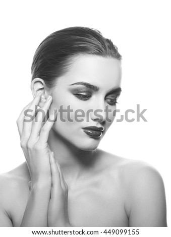 Beautiful face of young caucasian brunette woman with red glossy lips, intensive make-up, perfect skin and blue eyes isolated on white touch her skin. Studio portrait. Black and white - stock photo