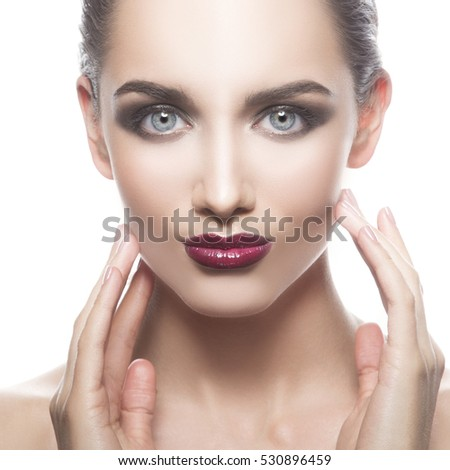 Beautiful face of young caucasian brunette woman with red glossy lips, intensive make-up, perfect skin and blue eyes isolated on white touch her skin. Studio portrait.