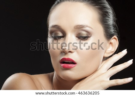Beautiful face of young caucasian brunette woman with red lips, evening make-up, perfect skin and choosy emotion. Isolated on black background. Studio portrait.