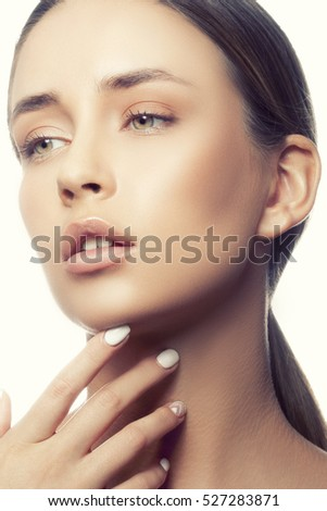 Beautiful face of young caucasian girl with natural make-up, perfect skin and green eyes touch her skin isolated on white background. Studio portrait. Toned