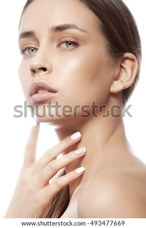 Beautiful face of young caucasian girl with natural make-up, perfect skin and green eyes touching her chin isolated on white background. Studio portrait.