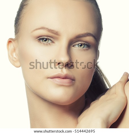 Beautiful face of young caucasian woman with natural make-up, perfect skin and green eyes isolated on white. Studio portrait. Toned