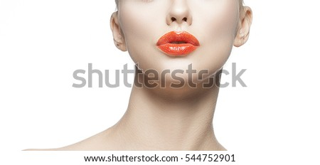 Beautiful face of young caucasian woman with natural make-up, perfect skin, bright red lips and green eyes touching her cheek isolated on white background. Studio portrait.