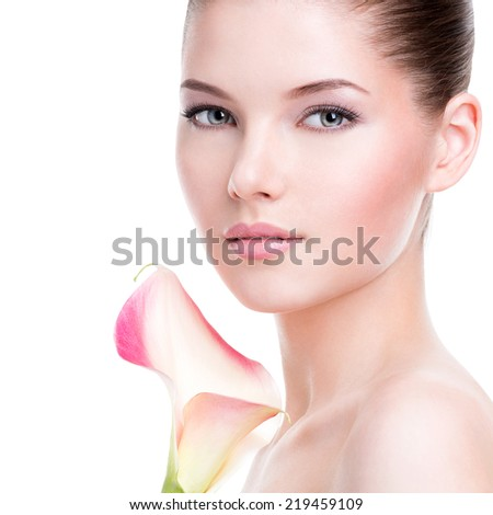 Beautiful face of young pretty woman with healthy skin and pink flowers on body - isolated on white. - stock photo