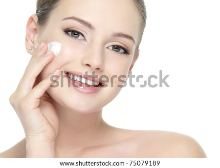 Beautiful face of young smiling woman applying cream on the cheek - white background - stock photo