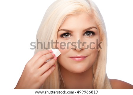 Beautiful face of young woman for Aesthetics facial skincare concept wiping applying makeup cosmetics, on white.