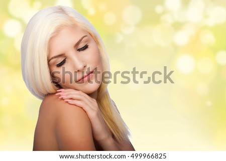 Beautiful face of young woman for Aesthetics facial skincare concept with eyes closed, hand on shoulder, on blurred lights background.