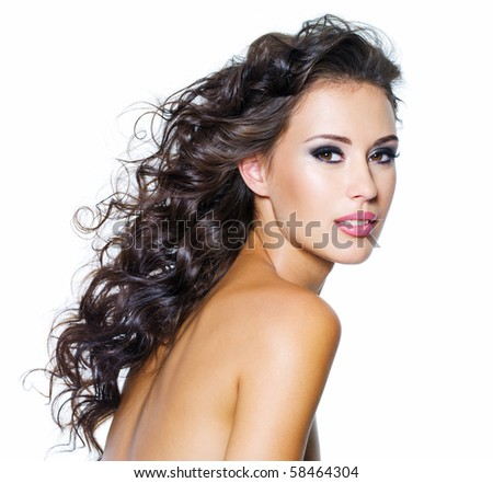 Beautiful face of young woman with clean skin. Girl with long curly hairs. Bright eye make-up - stock photo