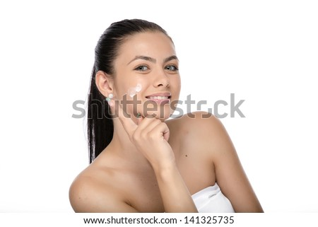 Beautiful face of young woman with cosmetic cream on a cheek. Closeup portrait isolated on white.
