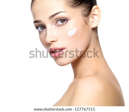 Beautiful face of young woman with cosmetic cream on a cheek. . Skin care concept. Closeup portrait isolated on white. - stock photo
