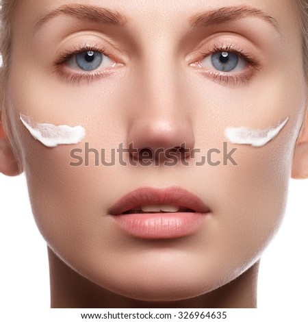 Beautiful face of young woman with cosmetic cream on a cheek. Skin care concept. Closeup portrait isolated on white. Close-up young beautiful face of girl applying moisturize cream. - stock photo