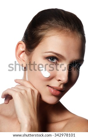 Beautiful face of young woman with cosmetic cream on a cheek. Skin care concept. Closeup portrait isolated on white. Close-up young beautiful face of girl applying moisturize cream - stock photo