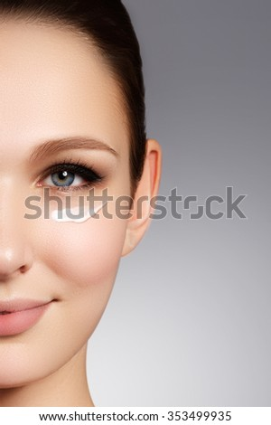 Beautiful face of young woman with cosmetic cream on a cheek. Skin care concept. Closeup portrait on beige background. Close-up young beautiful face of girl applying moisturize cream