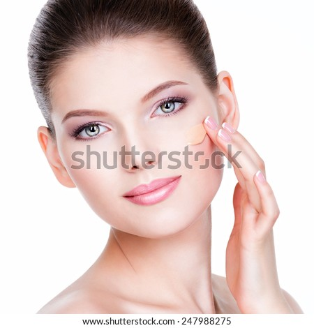 Beautiful face of young woman with cosmetic foundation on a skin over white background. Beauty treatment concept. - stock photo