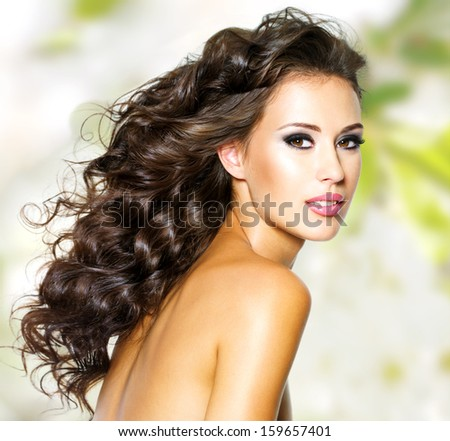 Beautiful face of young woman with long hairs bright makeup - stock photo