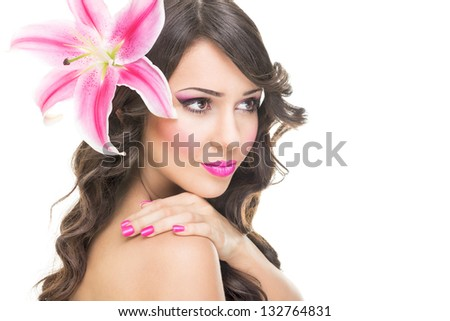 Beautiful face of young woman with pink lily flower - stock photo