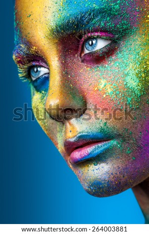 Beautiful face with colored powder on a blue background - stock photo