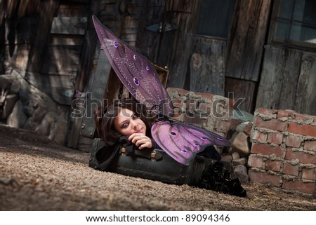 Beautiful faery rests on suitcase with black roses - stock photo