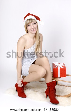 Beautiful fair haired young woman sitting on a sleigh - stock photo