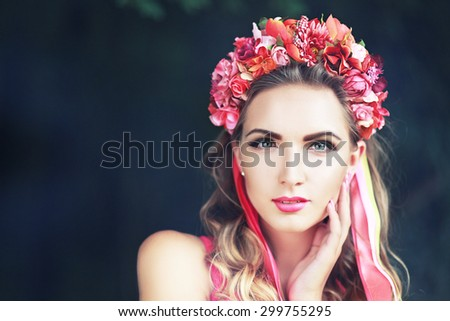 beautiful fairy: filtered image of brunette pretty girl in lotus flower crown and pink makeup posing gracefully on green outdoors copy space background - stock photo