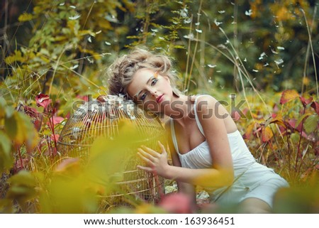 Beautiful fairy girl with golden cage in a forest - stock photo