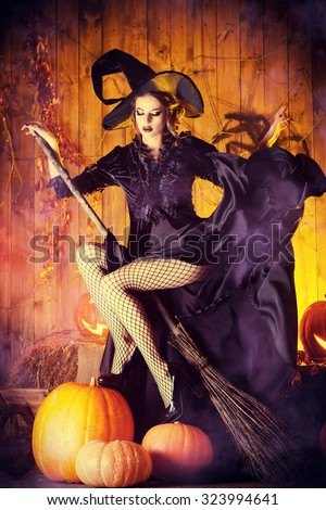 Beautiful fairy witch with her broom in a wooden barn with pumpkins. Halloween.