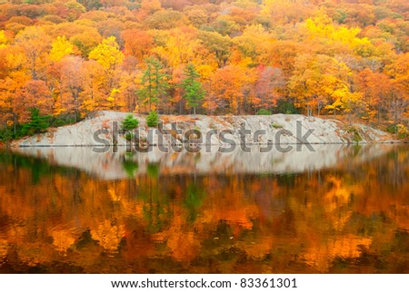 Beautiful fall colors reflecting in the forest lake. - stock photo