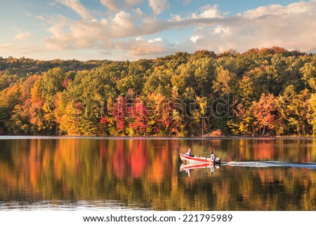 beautiful fall reflections in a lake with a fishing boat during sunset - stock photo