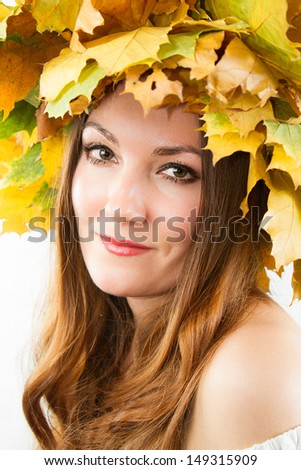 Beautiful fall woman. Portrait of girl with autumn wreath of maple leaves on head on isolated white background
