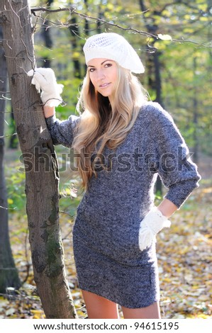 Beautiful fall women in white cap and gloves in the park - stock photo