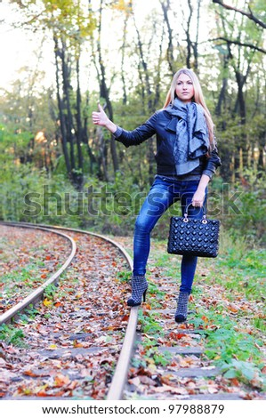 Beautiful fall women waiting train on a railroad - stock photo