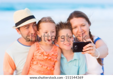 Beautiful family at beach making a self portrait with mobile phone - stock photo