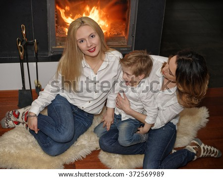 Beautiful family consisting of mother with ginger hair, daughter with blond hair and a son sitting on the fur carpet near fireplace. Fire in the fireplace is burning. - stock photo