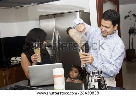Beautiful family cooking in kitchen with appliances and laptop