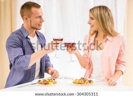 Beautiful family couple having dinner together. They are drinking wine and looking to each other in kitchen. - stock photo