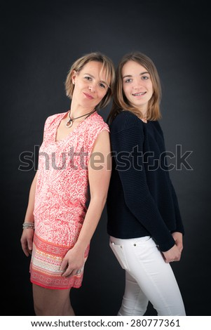 Beautiful family doing different expressions in different sets of clothes: back to back - stock photo