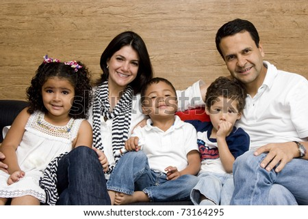 Beautiful family enjoying, mom and dad playing with their children at home - stock photo