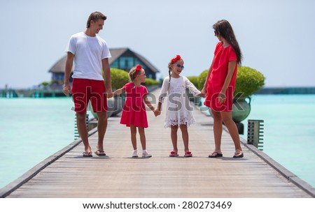 Beautiful family have fun on wooden jetty during summer vacation  - stock photo