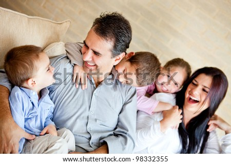 Beautiful family having fun at home sitting on the sofa - stock photo