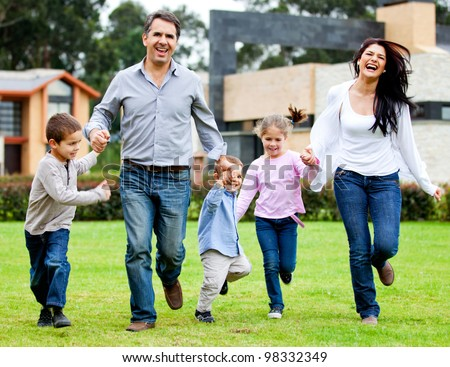 Beautiful family having fun running outdoors and smiling - stock photo
