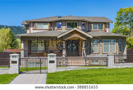 Beautiful family house in suburban of Vancouver on blue sky background. Luxury residential house with iron fence and green lawn in front.