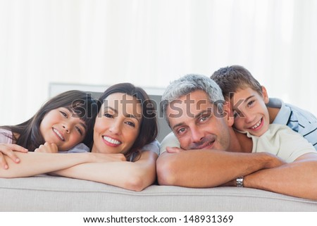 Beautiful family in sitting room smiling at camera at home - stock photo